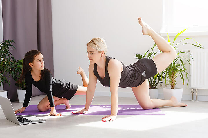 Mother and daughter doing yoga poses while watching laptop