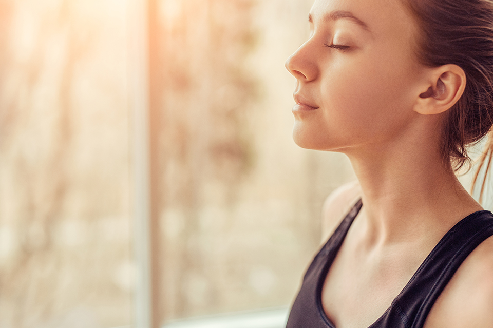 Woman taking deep breathe to deal with anxiety