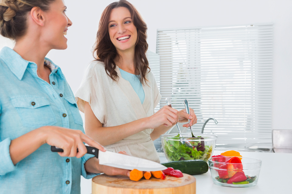 Two women happily prepare a healthy ketogenic meal