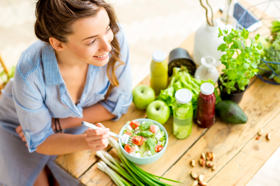 Woman eating salad in brightly lit room with other produce on the table