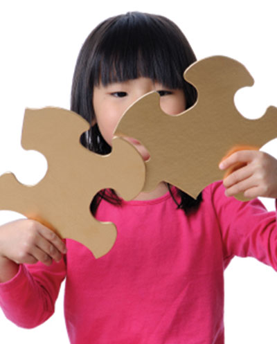 Young child attempting to put together two large puzzle pieces