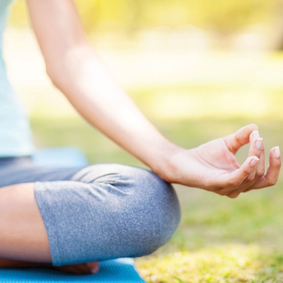 Woman sitting in lotus position and meditating