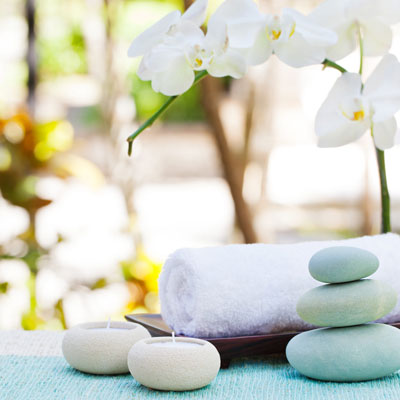 Spa environment with a towel, candles, flowers, and stones